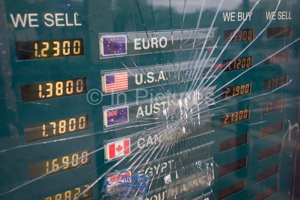 Cracked glass in a foreign currency exchange rates window. Currencies from the Eurozone and the USA, to Canada and Egypt, are displayed in the window of a post office in south London where customers are able to buy their foreign holiday money. The rates are there too for buying and selling notes and coins from countries abroad. The glass has been smashed, its cracks spreading out from the central point of impact, a metaphor for the cracks in the global economy.