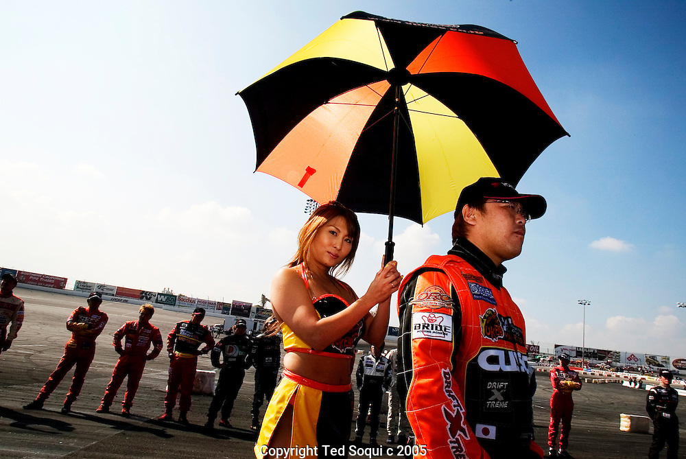Japanese Drift Champion car driver with a umbrella girl..Drift racing visits Irwindale Motor Speedway. Drift racing originated in Japan and is becoming very popular in the USA. The drivers are rated on their driving style. They must maintain control of their cars while driving them in a constant state of skid/burnout at around 100mph on a road course track. The cars are production cars with some modifications and are usually street legal..Irwindale Motor Speedway, CA USA .2/27/05.Photo by Ted Soqui c 2005