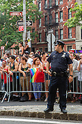 A New York City Police officer looks up the parade route on Christopher Street. This section of Christopher Street also bears the name Stonewall Place, after the Stone Wall Inn riots of 1969, the putative beginning the the gay rigts movement in the U.S.