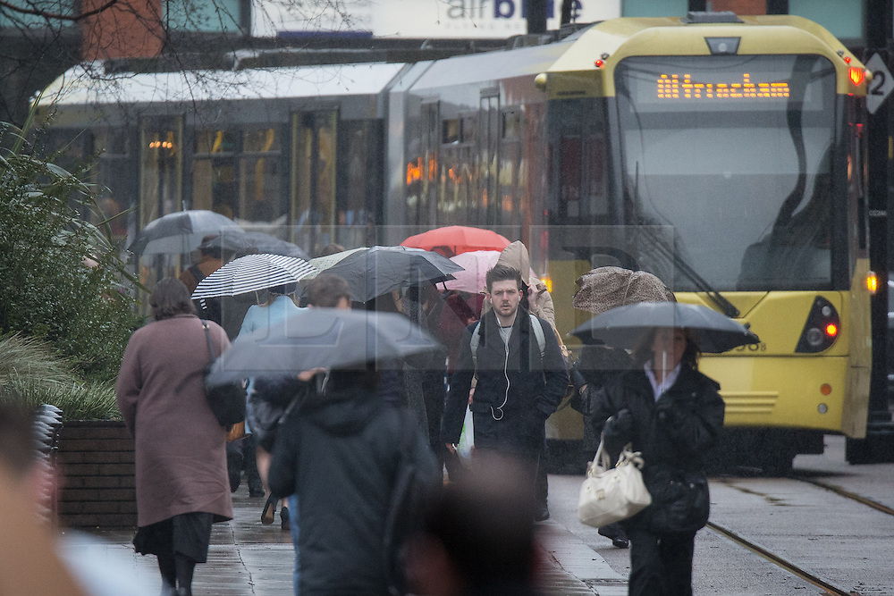 © Licensed to London News Pictures . 04/03/2014 . Manchester , UK . Commuters with umbrellas open walking to work in the rain this morning (Tuesday 4th March 2014) . Photo credit : Joel Goodman/LNP