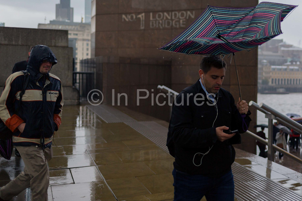 During a spring shower, a male commuter carrying a collapsed umbrella rushes over London Bridge during the evening rush-hour, from the City southwards to Southwark, on 3rd May, in London, England.