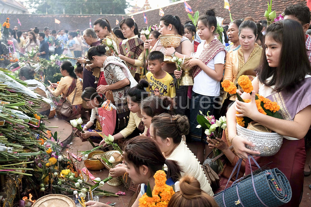 """Bringing offerings of flowers, incense sticks and candles to Buddha at the That Luang festival, Vientiane, Lao PDR. Pha That Luang is the national symbol and most important religious monument of Laos. Vientiane's most important Theravada Buddhist festival, """"Boun That Luang"""", is held here for three days during the full moon of the twelfth lunar month (November). Monks and laypeople from all over Laos congregate to celebrate the occasion with three days of religious ceremony followed by a week of festivities, day and night. The procession of laypeople begins at Wat Si Muang in the city centre and proceeds to Pha That Luang to make offerings to the monks in order to accumulate merit for rebirth into a better life. The religious part concludes as laypeople, carrying incense and candles as offerings, circumambulate Pha That Luang three times in honor of Buddha."""