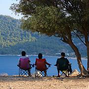 People sit in chairs and enjoy view of Kumlubuk beach and sea near Marmaris, Turkey