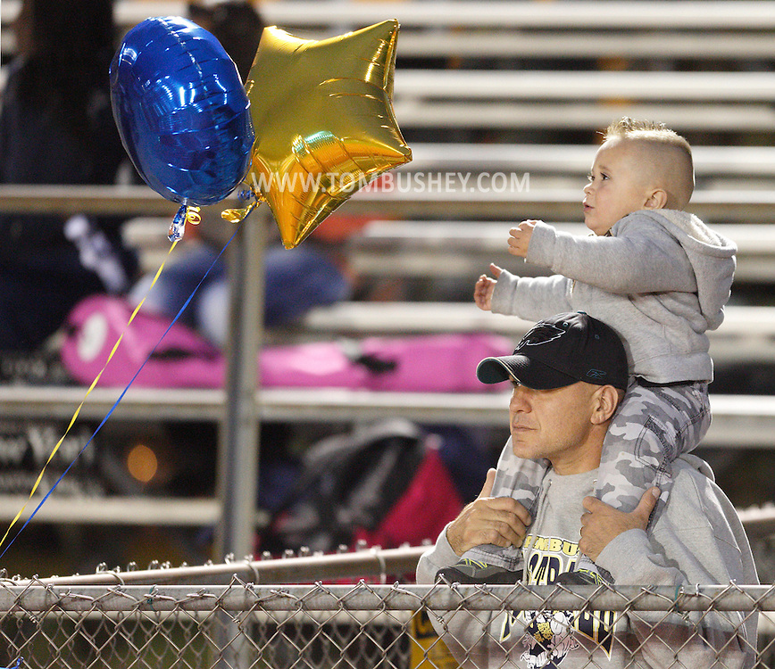 Madden Miranowicz, 2, reaches for two balloons while sitting on the shoulders of his father Paul Miranowicz during a football game between Middletown and Pine Bush at Pine Bush on Friday, Sept. 27, 2013.