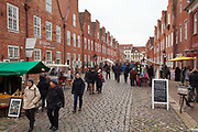 People looking at a street market. The Dutch Quarter is a famous area / neighbourhood of Potsdam. Built between 1733-40 and designed by Jan Borman, it is a centre for tourists visiting the town, consisting of many restaurants, cafes and boutique shops selling crafts and local food and drink. Potsdam, Brandenburg, Germany.