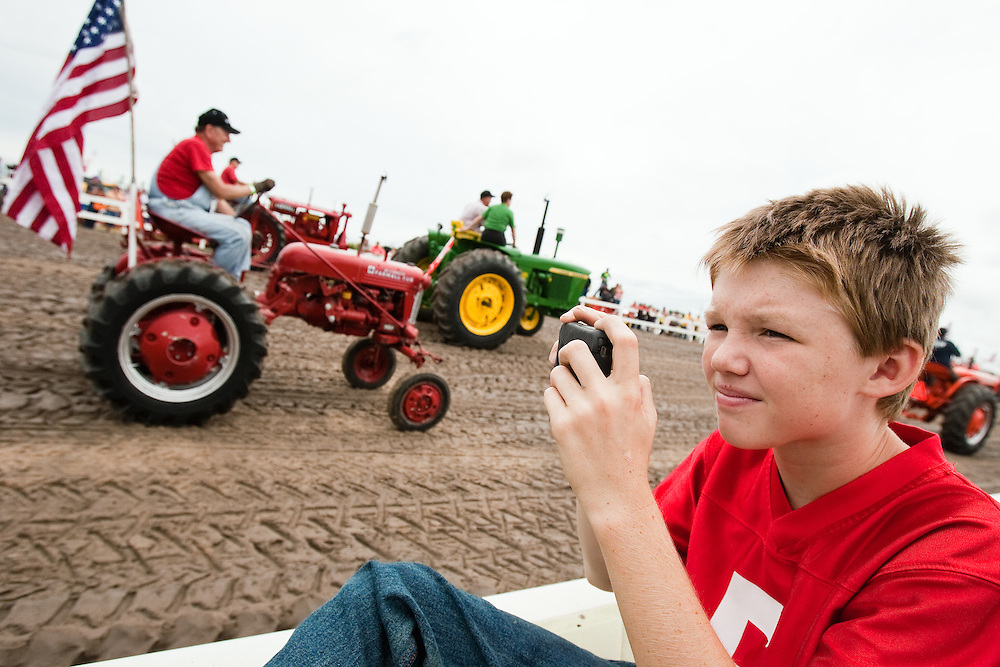 Dillion DeVore, 12, of Wood River snaps a picture on a phone during the classic tractor parade Saturday at Fonner Park Race Track. Over 1,000 tractors were registered in to attempt to break the world record for the largest parade of classic tractors.  (Independent/Matt Dixon)