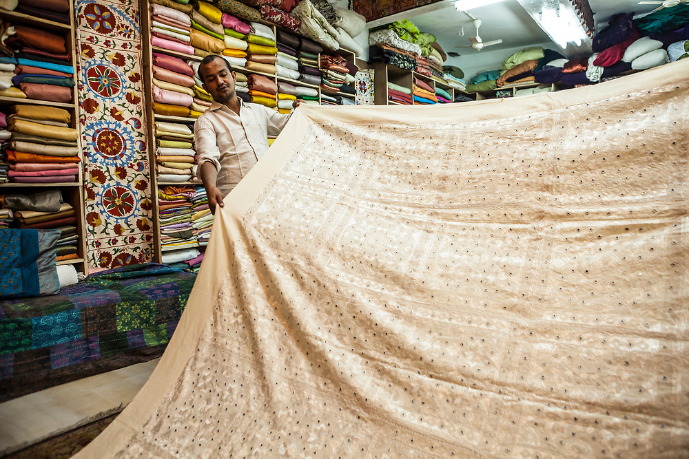 A salesman showing a bedspread / blanket with mirrors sewn into the intricate design, Jodhpur, Rajasthan, India.
