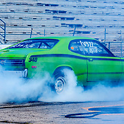 Muscle car performing a burnout at racetrack