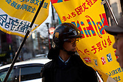 Flags belonging to activists marching for the release of, Fumiaki Hoshino flap around the facre of a riot policeman. Hoshino was arrested in 1975 for the alleged killing of a police officer during riots in Tokyo and sentenced to life imprisonment, diring a rally by left wing activists and trade unions. Tokyo, Japan. Sunday March 23rd 2014. The main organiser of the protest was The Farmers' League Against Narita Airport. Around 1,000 activists from this league and other unions took part.