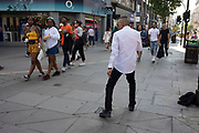 Young man dancing on Oxford Street in London, England, United Kingdom. Listening to music on his headphones this dancer was practicing his street dance moves on this busy shopping street.