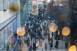 © Licensed to London News Pictures. 19/12/2020. Manchester, UK. Shoppers on Market Street, Manchester are seen through Christmas decorations. Photo credit: Kerry Elsworth/LNP