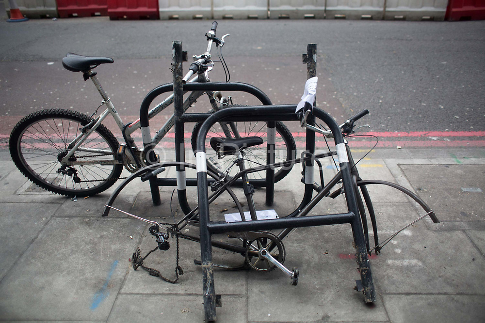 A chaotic mess of bikes and bike racks are left on the pavement 29th January 2016. Some bits have been stolen, others just dismantled. Riding bikes in London is a growing trend and mode of transport.