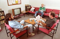 Multiracial group of men sitting in communal lounge in probation hostel,