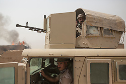 © Licensed to London News Pictures. 11/09/2015. Kirkuk, Iraq. Kurdish peshmerga man an armoured humvee in the village of Zankhar, Iraq. The village was taken by the peshmerga during an offensive to expand a safety zone around Kirkuk, Iraq.<br /> <br /> The offensive, which went unchallenged after ISIS left the area ahead of the attack, saw the peshmerga capture 15 villages along the Kirkuk front line. The objective of the offensive was to expand the safety zone around Kirkuk, stopping militants from firing missiles and rockets in to the city of Kirkuk. 3 peshmerga were killed and 24 wounded due to improvised explosive devices left behind by the militants. Photo credit: Matt Cetti-Roberts/LNP