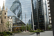 Angled view of the cityscape and skyline reflections looking towards 1 St Mary Axe aka the Gherkin as city wokers in small numbers interact in the quiet urban landscape on 26th May 2021 in London, United Kingdom. As the coronavirus lockdown continues its process of easing restrictions, the City remains far quieter than usual, which asks the question if normal numbers of people and city workers will ever return to the Square Mile.