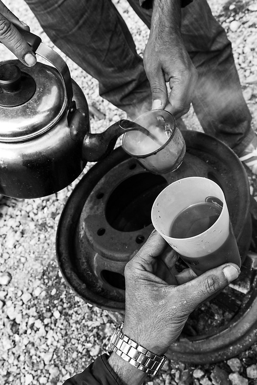 Morning coffee. Sharing a drink around a small stove with the men.