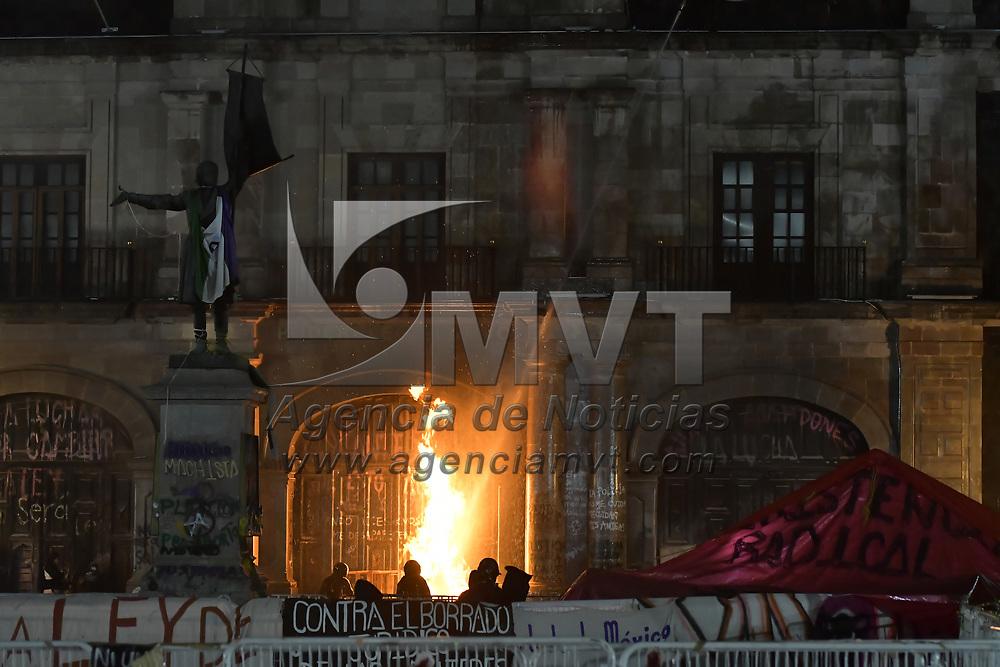 Toluca, México.- Elementos de seguridad del Congreso del Estado de México lanzan chorros de agua desde el techo del inmueble para intentan sofocar el fuego de la fachada de la cámara de diputados provocado por  el grupo de feministas  radicales que permanecen en plantón desde hace casi tres meses.. Agencia MVT / Arturo Hernández.