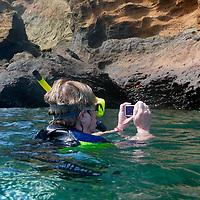 South America, Ecuador, Galapagos Islands, Bartholomew Island. A snorkeller in the bay at Pinnacle Rock.