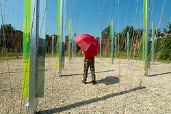"""© Licensed to London News Pictures. 20/07/2021. FOLKESTONE, UK. A person sheltering from the sun under an umbrella views """"Green/Light (For M.R.)"""", 2014, by Jyll Bradley a sculptural light installation created on a former Gasworks site. Preview of The Plot exhibition, the fifth Creative Folkestone Triennial. Folkestone has no publicly subsidised art gallery, so artists were invited to use public spaces to create new artworks in the seaside town. Over 20 works by artists including Assemble, Rana Begum, Gilbert & George, Atta Kwami, Pilar Quinteros, and Richard Deacon are on display 22 July to 2 November 2021.  Photo credit: Stephen Chung/LNP"""