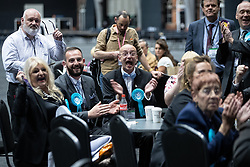 © Licensed to London News Pictures . 26/05/2019. Manchester, UK. Kevin Moore (central wearing glasses) at the North West European Election coun, Who has been sacked from The Brexit Party after it was discovered that he previously stood for the BNP. Brexit Party supporters cheer as they see results declared on televisions at the count . The count for seats in the constituency of North West England in the European Parliamentary election , at Manchester Central convention centre . Photo credit: Joel Goodman/LNP