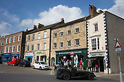 Richmond is a market town and the centre of the district of Richmondshire. Historically in the North Riding of Yorkshire, it is situated on the edge of the Yorkshire Dales National Park. North Yorkshire, England, UK. Local shops and streets in Trinity Church Square.