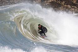 © Licensed to London News Pictures. 23/05/2020. Padstow, UK. A bodyboarder surfs inside the barrel of a wave near Padstow, Cornwall. There is currently no RNLI Lifeguard service in the county due to Coronavirus (Covid-19). The county has experienced unusual combination of large swell and warm weather during the bank holiday weekend. Photo credit : Tom Nicholson/LNP