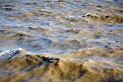 Choppy murky brown sea water carrying heavy sediment load, Dovercourt, Harwich, Essex, England