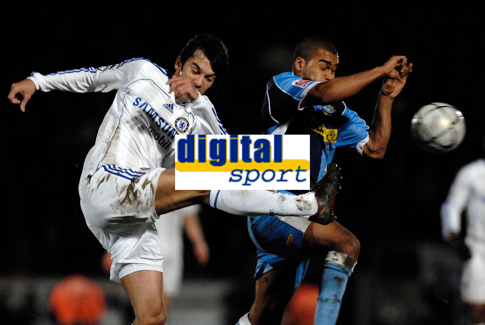 Photo: Richard Lane.<br />Wycombe Wanderers v Chelsea. Carling Cup, Semi Final 1st Leg. 10/01/2007. <br />Chelsea's Paulo Ferreira clears as Wycombe's Jermaine Easter challenges.