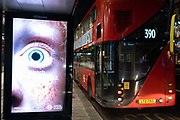 An advert from TFL Transport for London featuring a dilated pupil is displayed next to a London bus in Victoria, on 2nd February 2021, in London, England.
