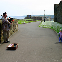 Europe, Great Britain, United Kingdom, Scotland, St. Andrews. Bagpiper and toddler.