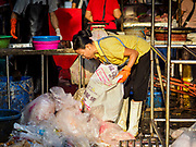 "04 DECEMBER 2018 - BANGKOK, THAILAND:  A worker sorts discarded single use plastic bags in Khlong Toei market. The issue of plastic waste became a public one in early June when a whale in Thai waters died after ingesting 18 pounds of plastic. In a recent report, Ocean Conservancy claimed that Thailand, China, Indonesia, the Philippines, and Vietnam were responsible for as much as 60 percent of the plastic waste in the world's oceans. Khlong Toey (also called Khlong Toei) Market is one of the largest ""wet markets"" in Thailand. December 4 was supposed to be a plastic free day in Bangkok but many market venders continued to use plastic.    PHOTO BY JACK KURTZ"