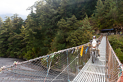 Biltwell's mechanic and special projects guy Rob Galan of Rouserworks riding across a suspension bridge on a Royal Enfield Himalayan in Motorcycle Sherpa's Ride to the Heavens motorcycle adventure in the Himalayas of Nepal. On the fourth day of riding, we went from Kalopani to Muktinath. Thursday, November 7, 2019. Photography ©2019 Michael Lichter.