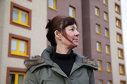 Woman standing outside a block of modern flats,