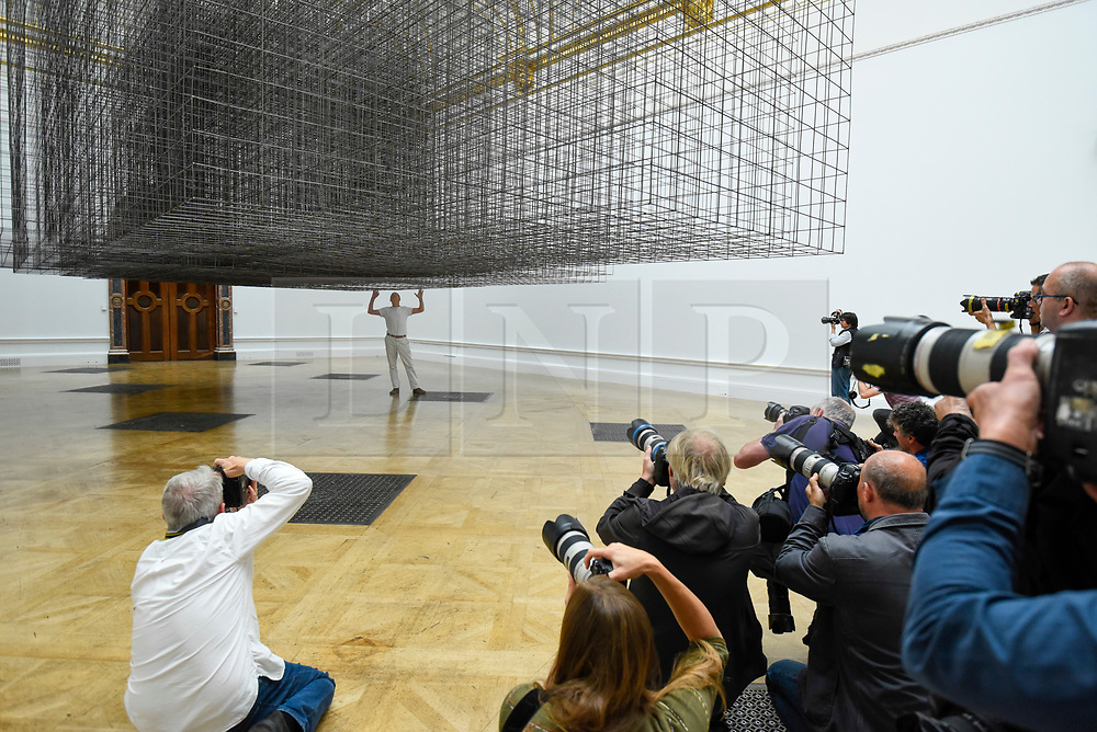 """© Licensed to London News Pictures. 16/09/2019. LONDON, UK.  Antony Gormley RA poses next to his work """"Matrix III"""", 2019, viewed by press photographers.  Preview of a new exhibition by Antony Gormley at the Royal Academy of Arts.  The show bring together existing and specially conceived new works from drawing to sculptures to experimental environments to be displayed in all 13 rooms of the RA's Main Galleries 21 September to 3 December 2019.  Photo credit: Stephen Chung/LNP"""