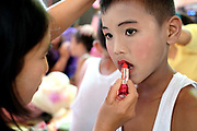 Applying make-up in preparation for a Shinbyu Novice Ceremony on 21st March 2016 in Mo Bye village, Shan State, Myanmar. In Myanmar, it is customary for boys to enter the monastery as a Buddhist novice between the age of ten and 20 years old although they can be as young as four, for at least one week.