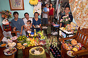 (MODEL RELEASED IMAGE) The Cabaña family in the main room of their 200-square-foot apartment in Manila, the Philippines, with a week's worth of food. Seated are Angelita Cabaña, 51, her husband, Eduardo Cabaña, 56 (holding sleeping grandson Dave, 2), and their son Charles, 20. Eduardo, Jr., 22 (called Nyok), his wife Abigail, 22, and their daughter Alexandra, 3, stand in the kitchen. Behind the flowers is the youngest son, Christian, 13 (called Ian). The Cabaña family is one of the thirty families featured in the book Hungry Planet: What the World Eats (p. 234).