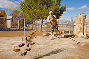 24 JANUARY 2010 -- WENDEN, AZ:  Leopoldo Portugal (CQ) cleans up the yard of his home in Wenden. Wenden was slammed by its second 100 year flood in 10 years on Thursday night when water raced through Centennial Wash and into the small town in La Paz County west of Phoenix. Most of the town's residents were evacuated to Red Cross shelters in Salome, about 5 miles west of Wenden.  PHOTO BY JACK KURTZ