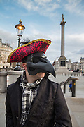 Man wearing Venician mask clearing pedestrians on a deserted Trafalgar Square as Coronovirus clampdown began on Friday evening rush hour,20th March 2020 in London, United Kingdom. The man, in a completely unofficial capacity, was encouraging people to go home to and keep 2 metres apart.