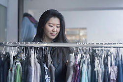 Young woman choosing clothes from clothes rack in clothing store, Freiburg Im Breisgau, Baden-w¸rttemberg, Germany