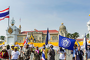 """09 DECEMBER 2013 - BANGKOK, THAILAND:  Anti-government students fly their school flag in of Government House in Bangkok. Thai Prime Minister Yingluck Shinawatra announced she would dissolve the lower house of the Parliament and call new elections in the face of ongoing anti-government protests in Bangkok. Hundreds of thousands of people flocked to Government House, the office of the Prime Minister, Monday to celebrate the collapse of the government after Yingluck made her announcement. Former Deputy Prime Minister Suthep Thaugsuban, the organizer of the protests, said the protests would continue until the """"Thaksin influence is uprooted from Thailand."""" There were no reports of violence in the protests Monday.     PHOTO BY JACK KURTZ"""
