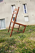 broken chair in the front yard of residential housing