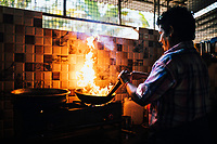Alleppey, India -- February 19, 2018: A man fries up a local fish curry at his small family run restaurant in the backwaters.