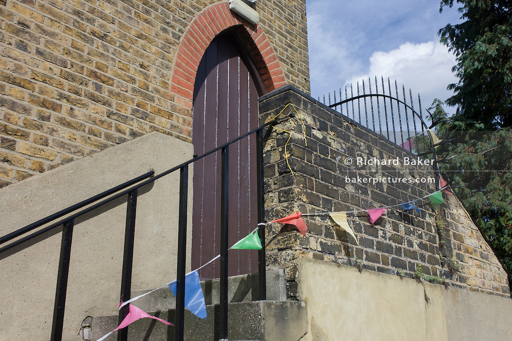 Fading bunting strung along the wall of a local church side entrance in south London.