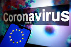 The European Union logo seen displayed on a mobile phone with an illustrative model of the Coronavirus displayed on a monitor in the background. Photo credit should read: James Warwick/EMPICS Entertainment