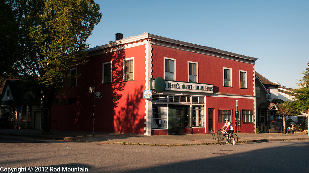 The early morning sun illuminates Benny's Market as a cyclist rides by. Vancouver, B.C.<br /> <br /> Photo: © Rod Mountain