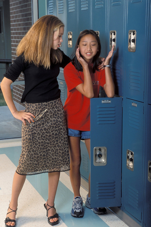 Anglo middle school girl comforts Asian friend in hallway of Pflugerville, Texas.<br /> ©Bob Daemmrich/