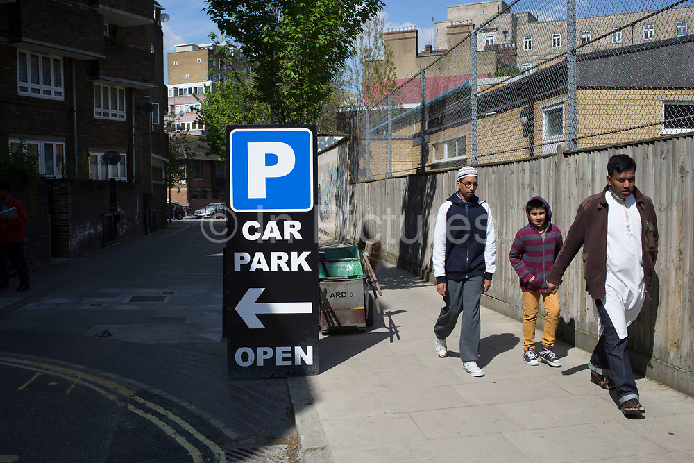 People from the Asian community in Euston walk past a car park sign. In this area, known as Somers Town, there is a well established North Indian community. London, UK.