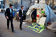 Businessmen in suits pass tents and signs containing slogans at the Occupy London OLSX protest site at St. Paul's, London, UK. The site is slowly being cleared, although some are staying until they are evicted, possibly within the coming days. The 'Occupy' movement spread via social media. The protests have been organised on social media pages that between them have picked up more than 15,000 followers.