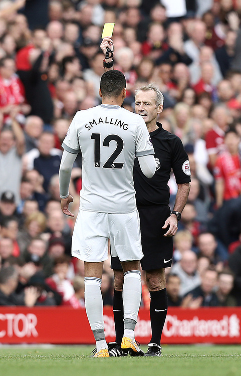 Manchester United's Chris Smalling is shown a yellow card by Referee Martin Atkinson<br /> <br /> Photographer Rich Linley/CameraSport<br /> <br /> The Premier League - Liverpool v Manchester United - Saturday 14th October 2017 - Anfield - Liverpool<br /> <br /> World Copyright © 2017 CameraSport. All rights reserved. 43 Linden Ave. Countesthorpe. Leicester. England. LE8 5PG - Tel: +44 (0) 116 277 4147 - admin@camerasport.com - www.camerasport.com