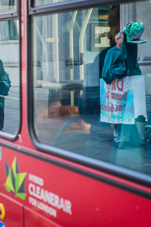 A puppet Draxosaurus is reflected in the window of a 'green' bus. It symbolises their view that Drax should be extinct technology or at least shoul be axed - #AxeDrax protest outside the annual Drax shareholder AGM. Protestors demanded cleaner, greener energy generation systems. They continued on to the Department of Energy and Climate Change to deliver a petition demanding that subsidies given to Drax, for burning biomass, be stopped for making climate change worse.